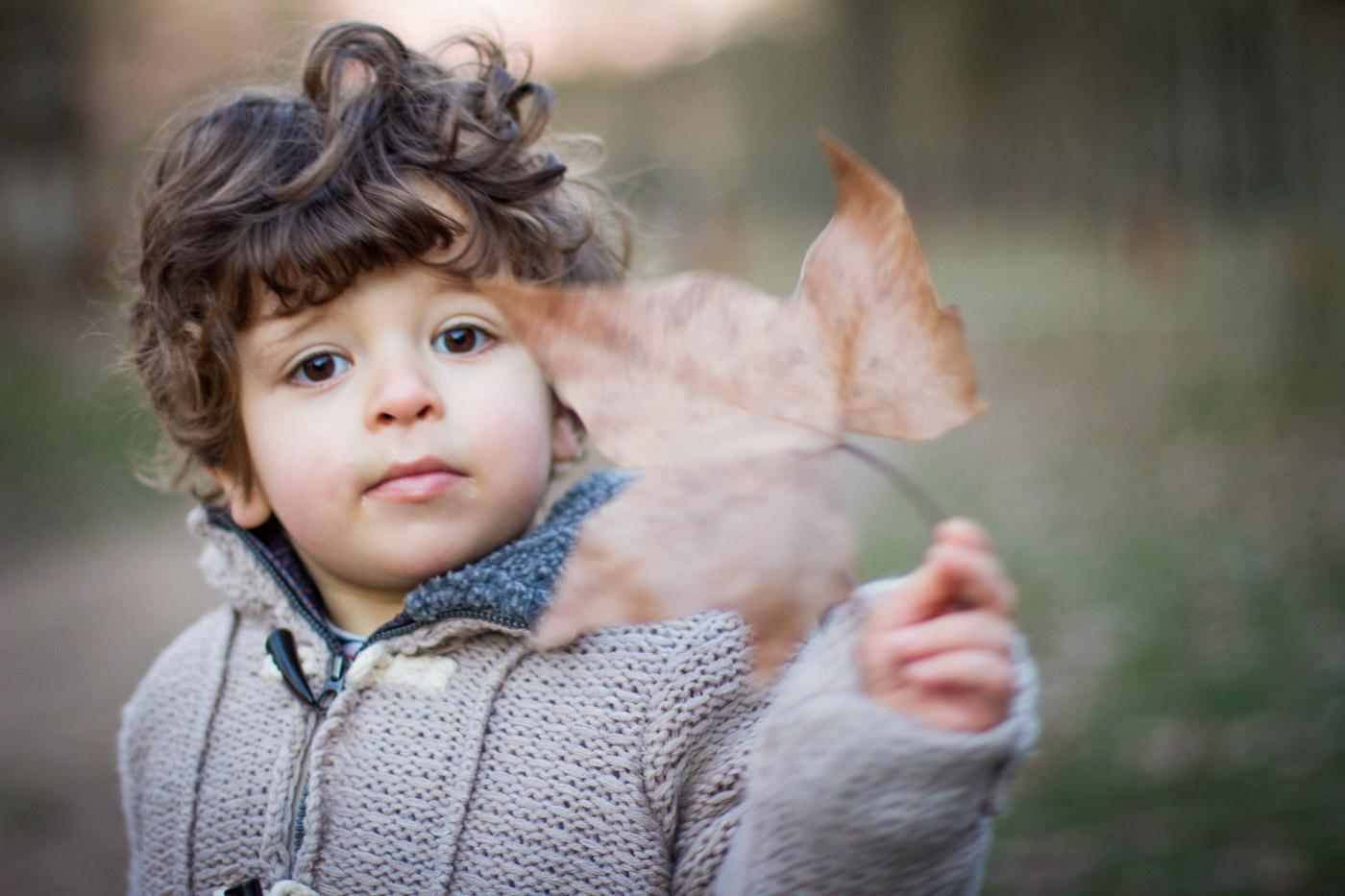Niño que sujeta una hoja seca