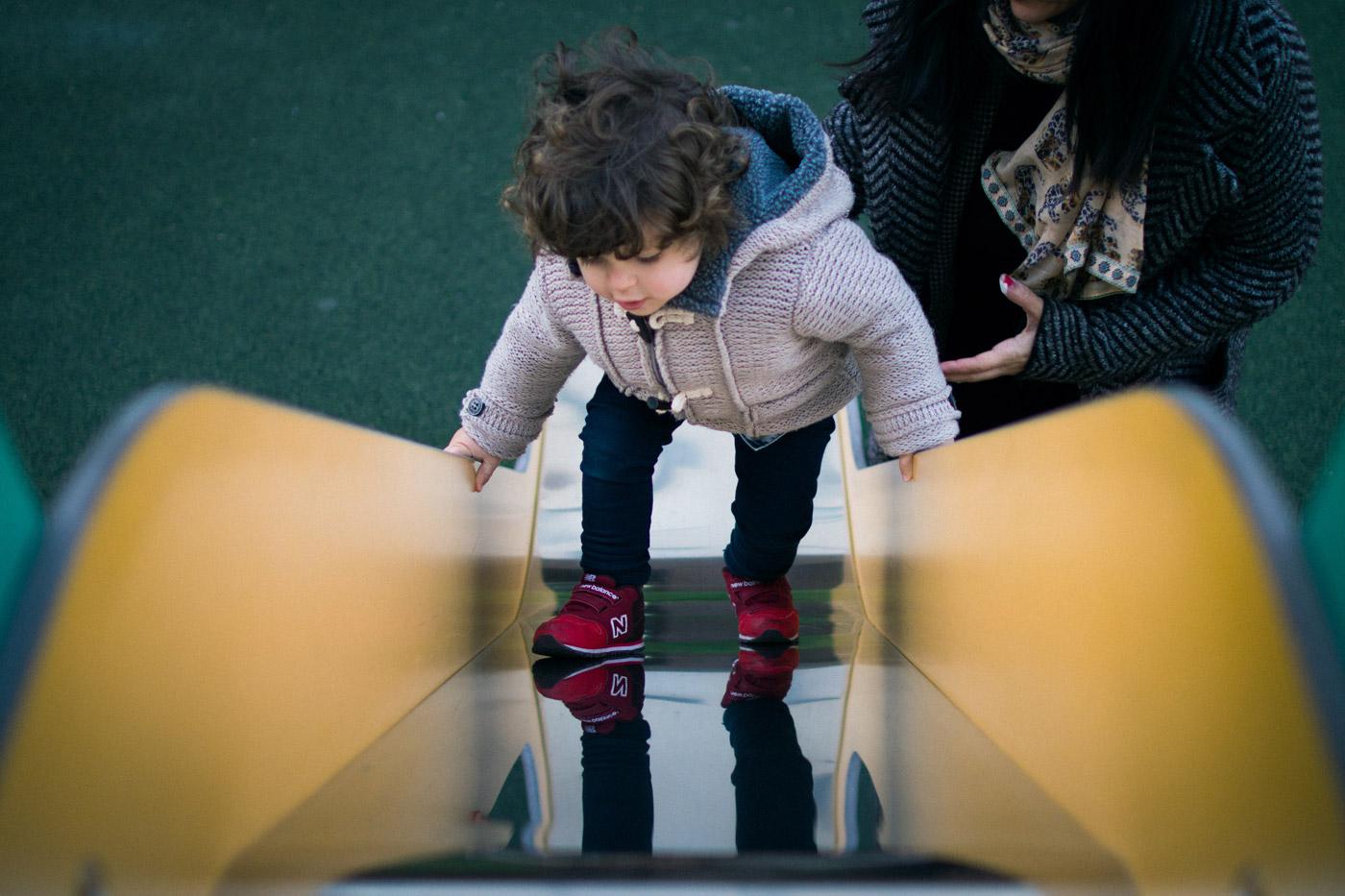 niño subiendo un tobogán al revés con la mano protectora de su madre