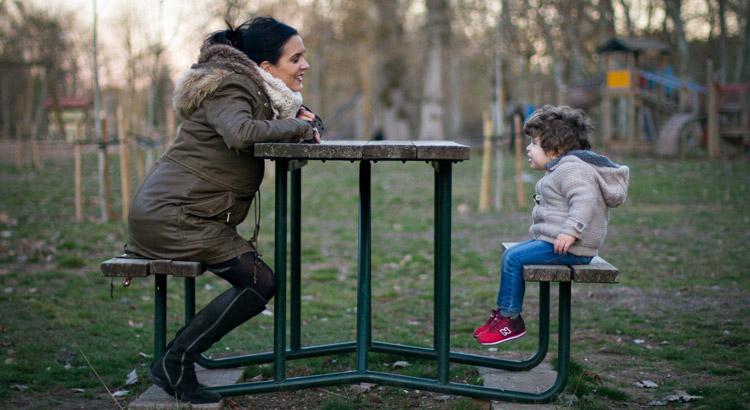 madre y hijo jugando en una mesa al parque