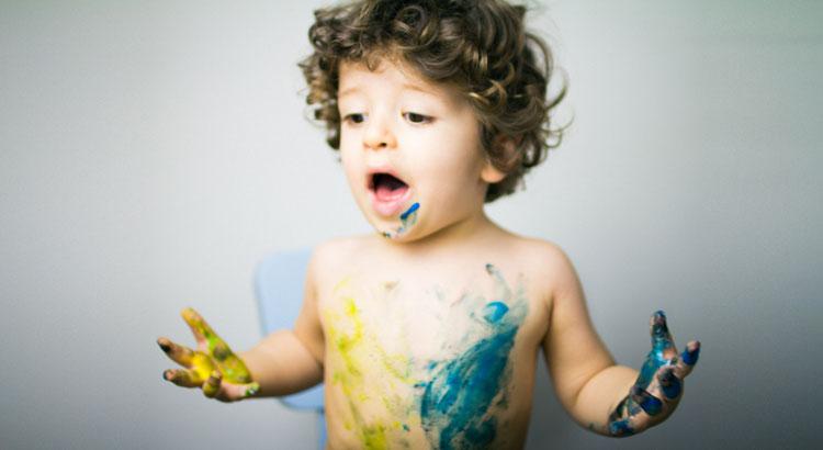 niño con pintura acuarela haciendo body painting