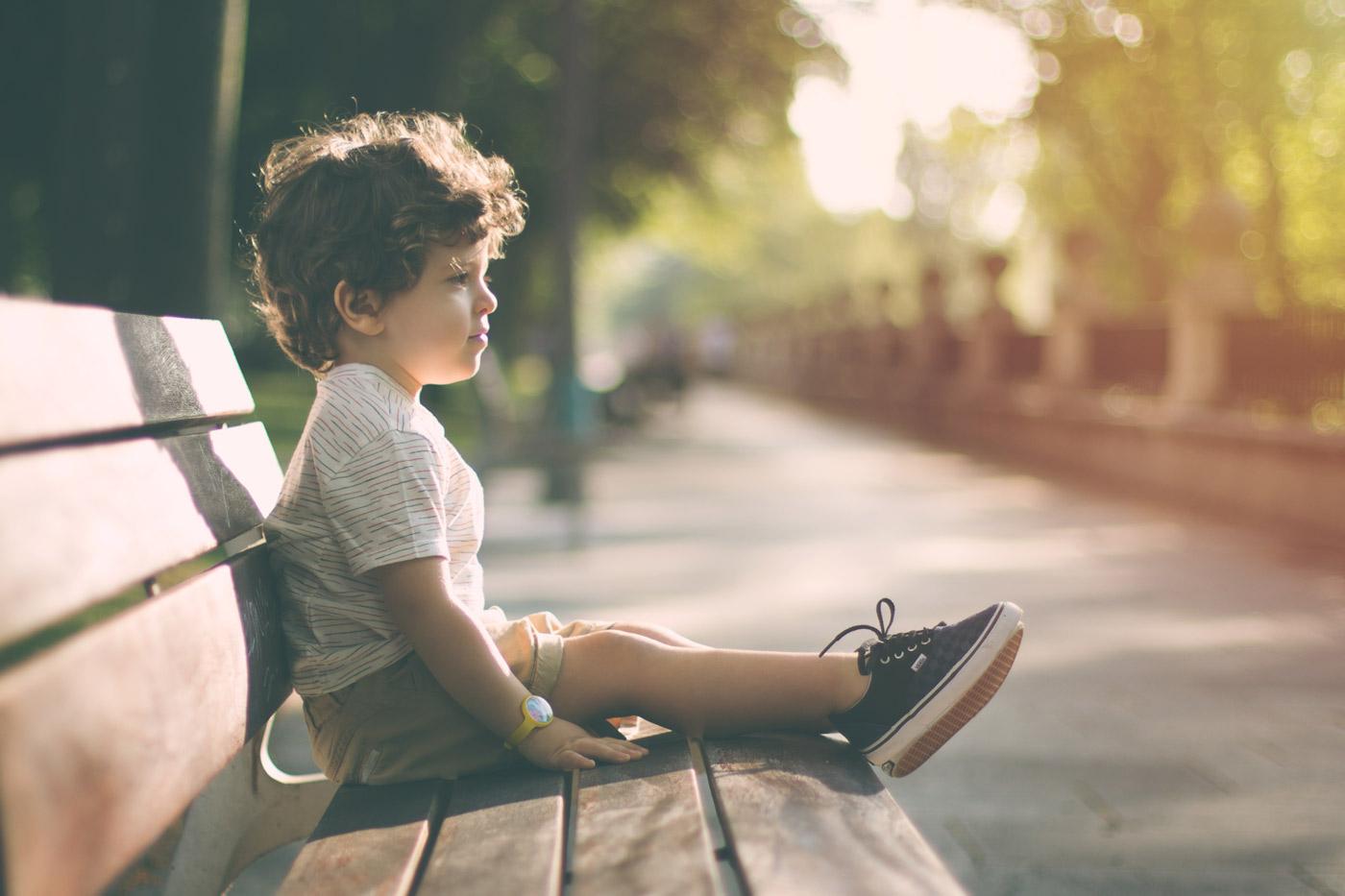 niño sentado en un banco iluminado por la luz dorada del sol