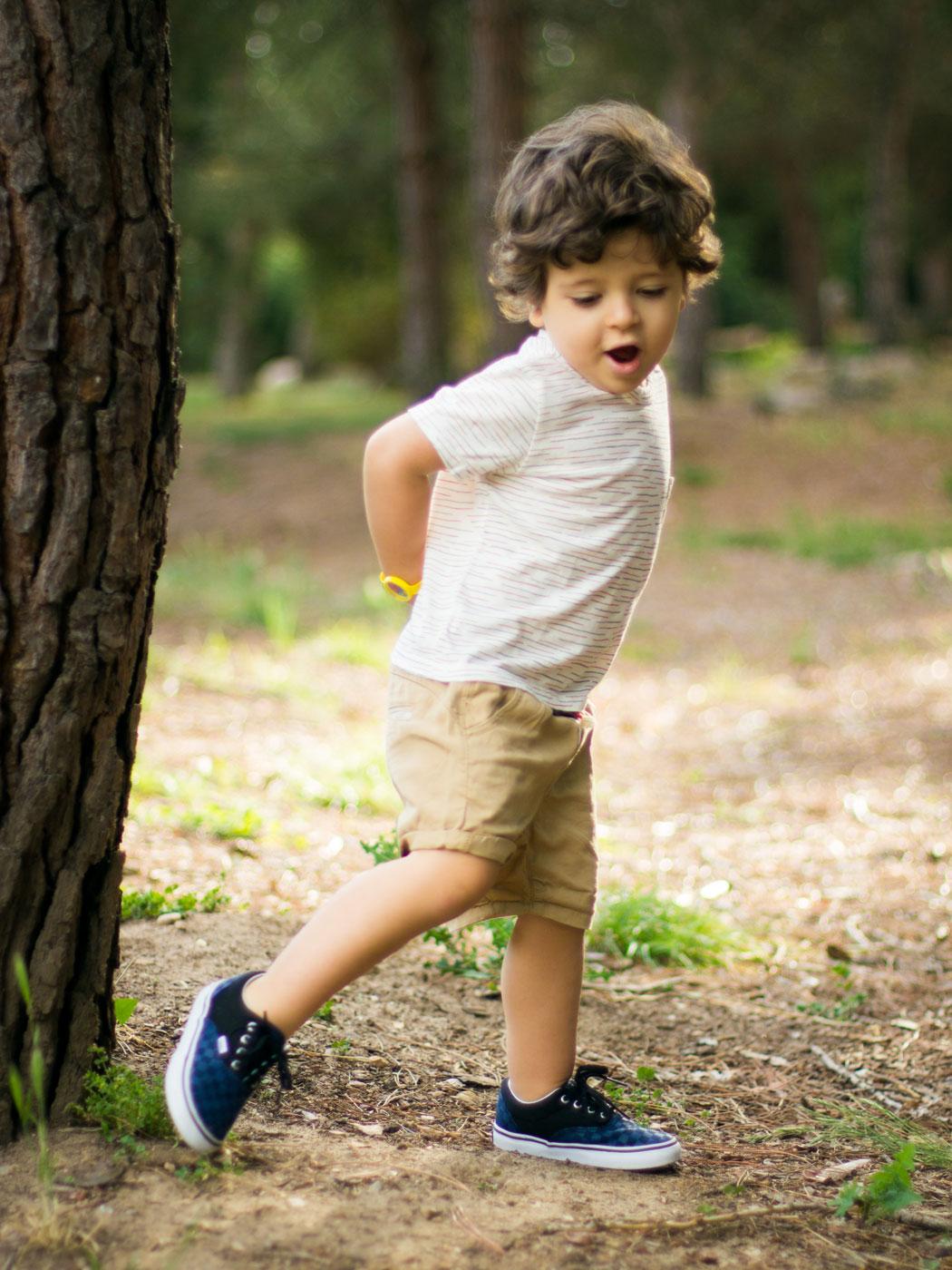 niño corriendo feliz en el campo con un arbol