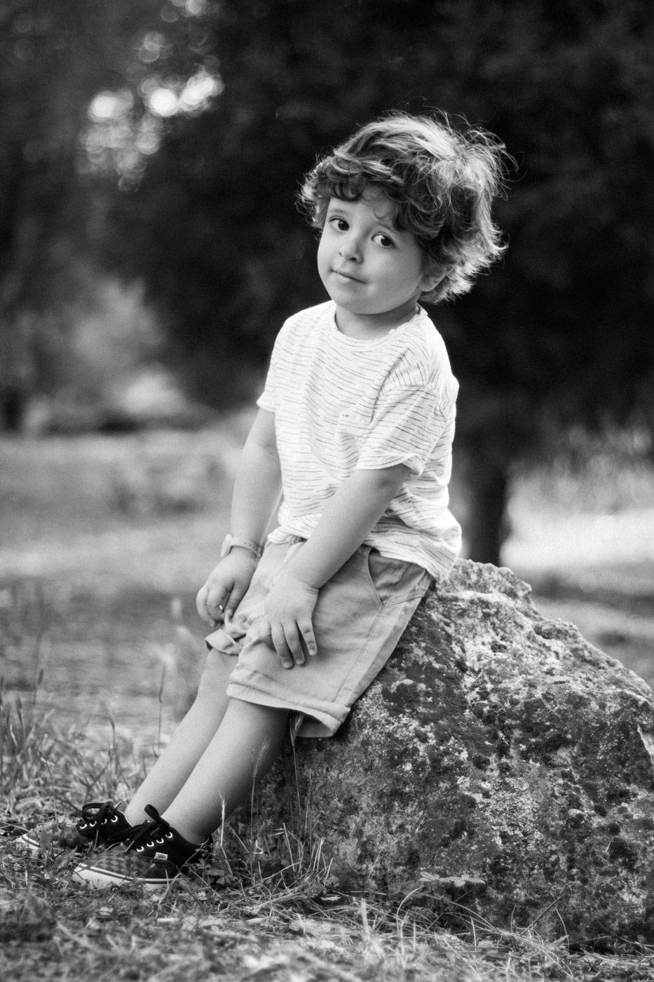 niño sentado en una piedra en el campo en blanco y negro