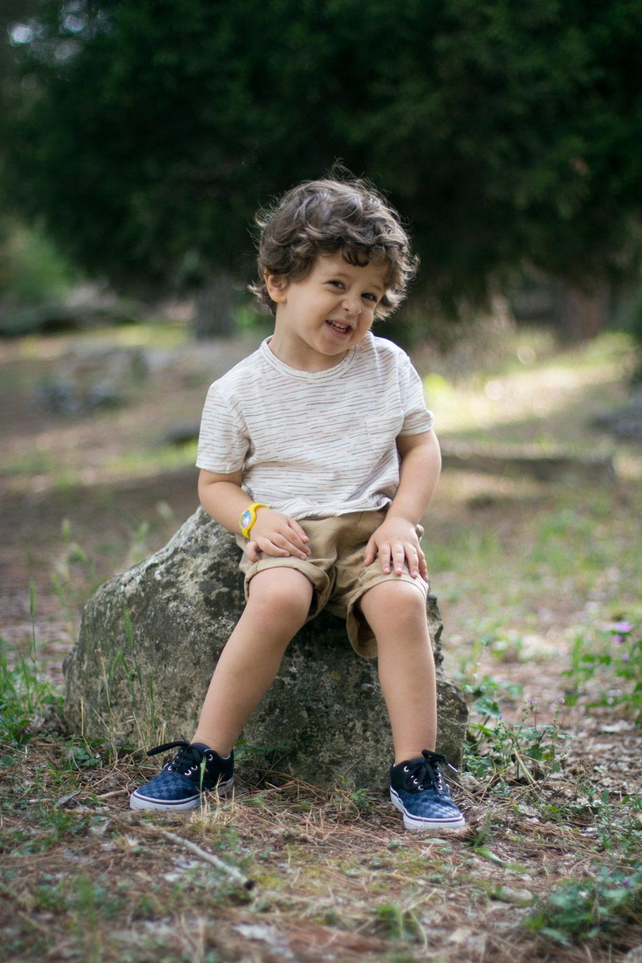 niño sentado en una roca en el parque urbano