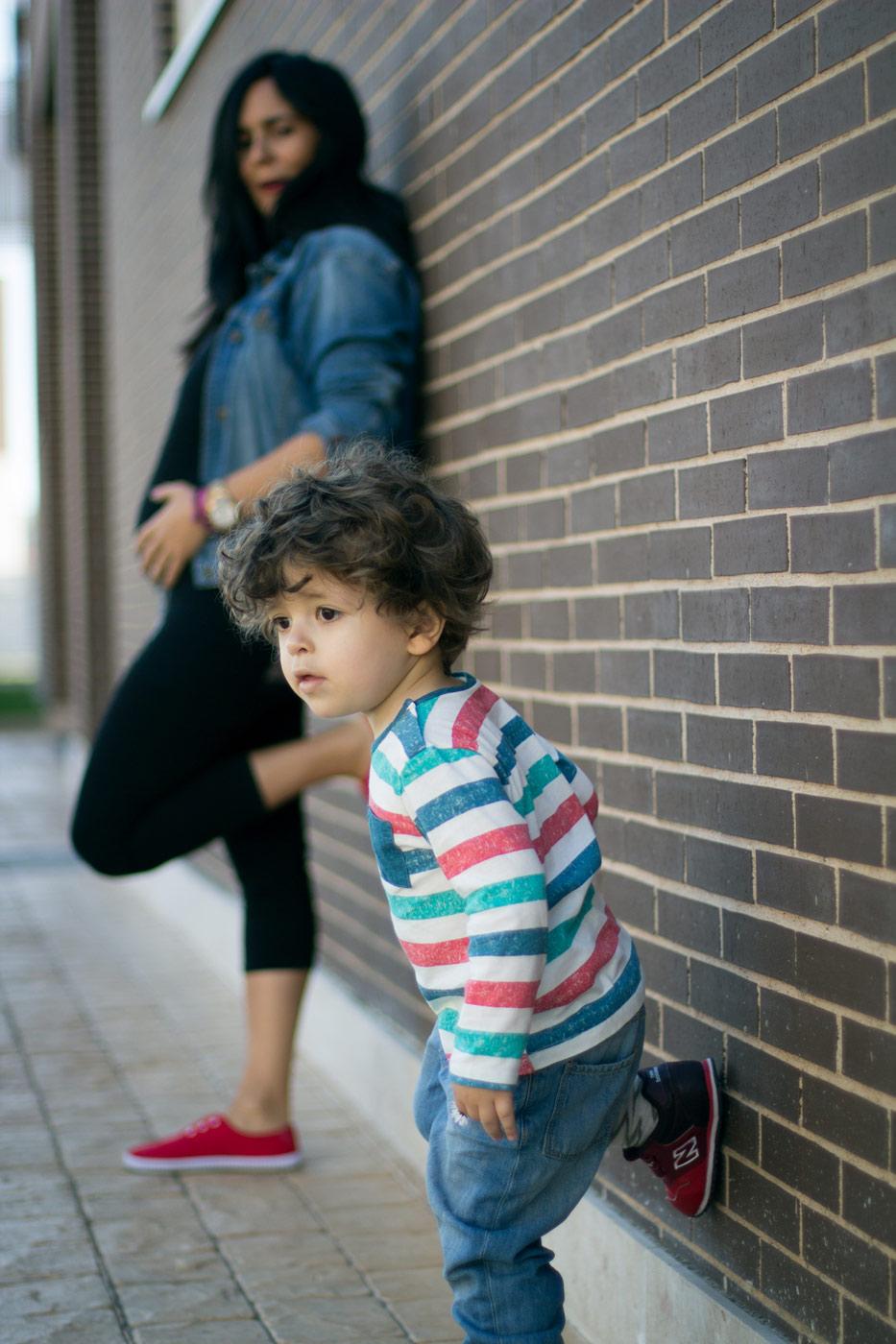 niño de dos años imitando su madre embarazado apoyandose los dos en una pared de ladrillos