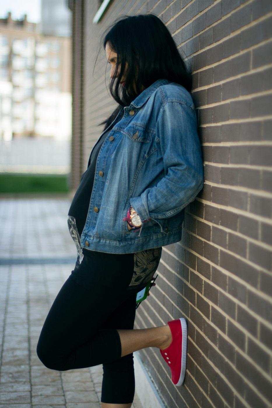 mujer embarazada apoyada en una pared de ladrillos