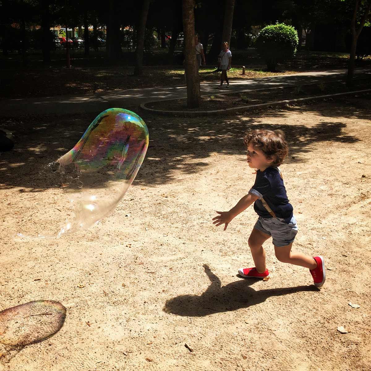 niño que corre detrás de una burbuja gigante