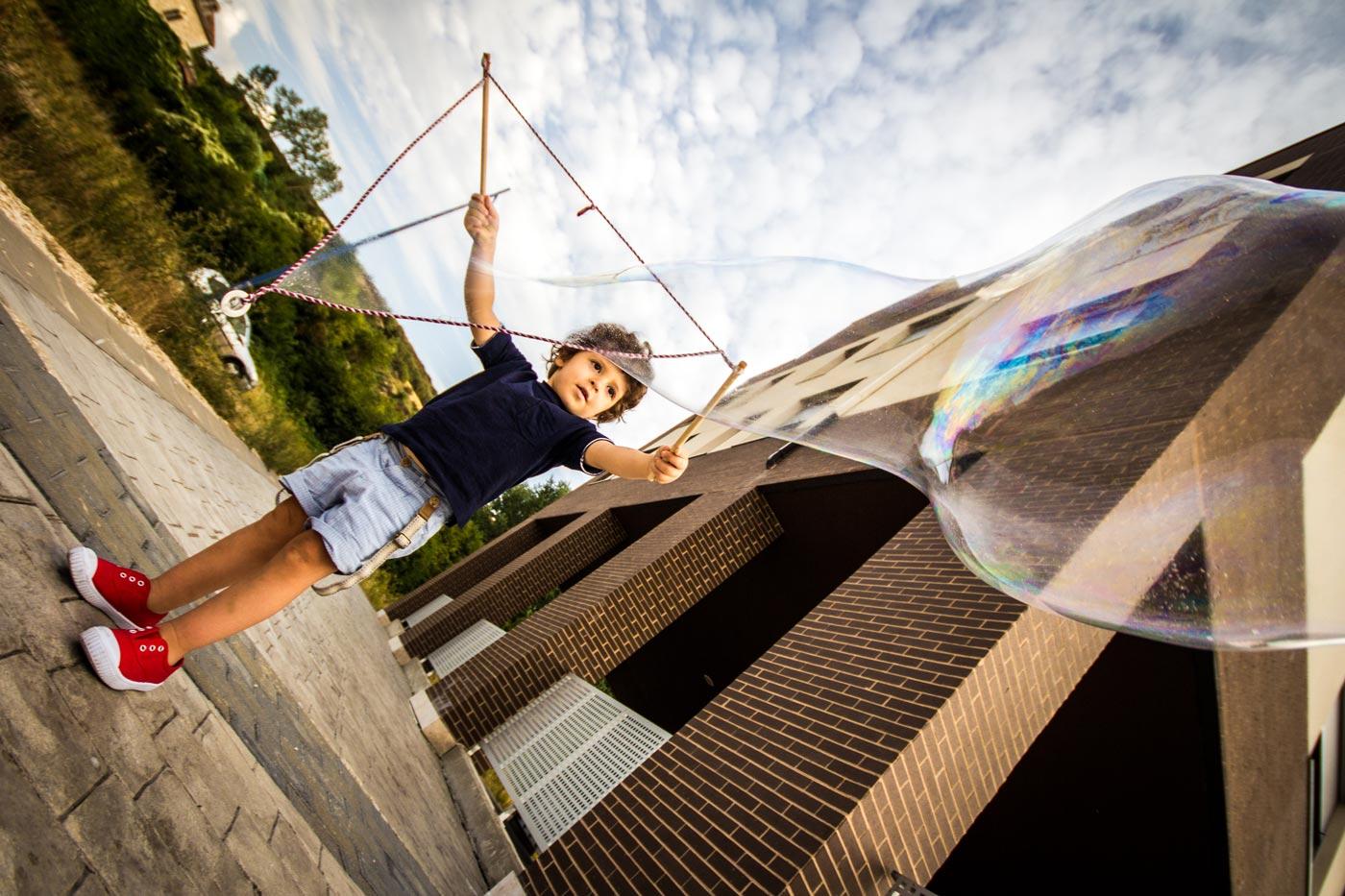 niño que hace una burbuja gigante en los soportales