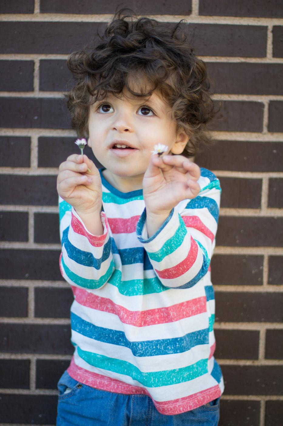 niño felic con dos pequeñas margaritas en las manos