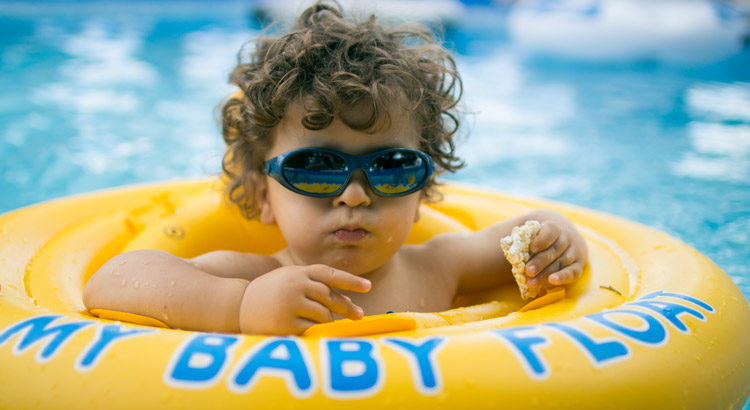 bebe en flotador en una piscina comiendo galletas saladas