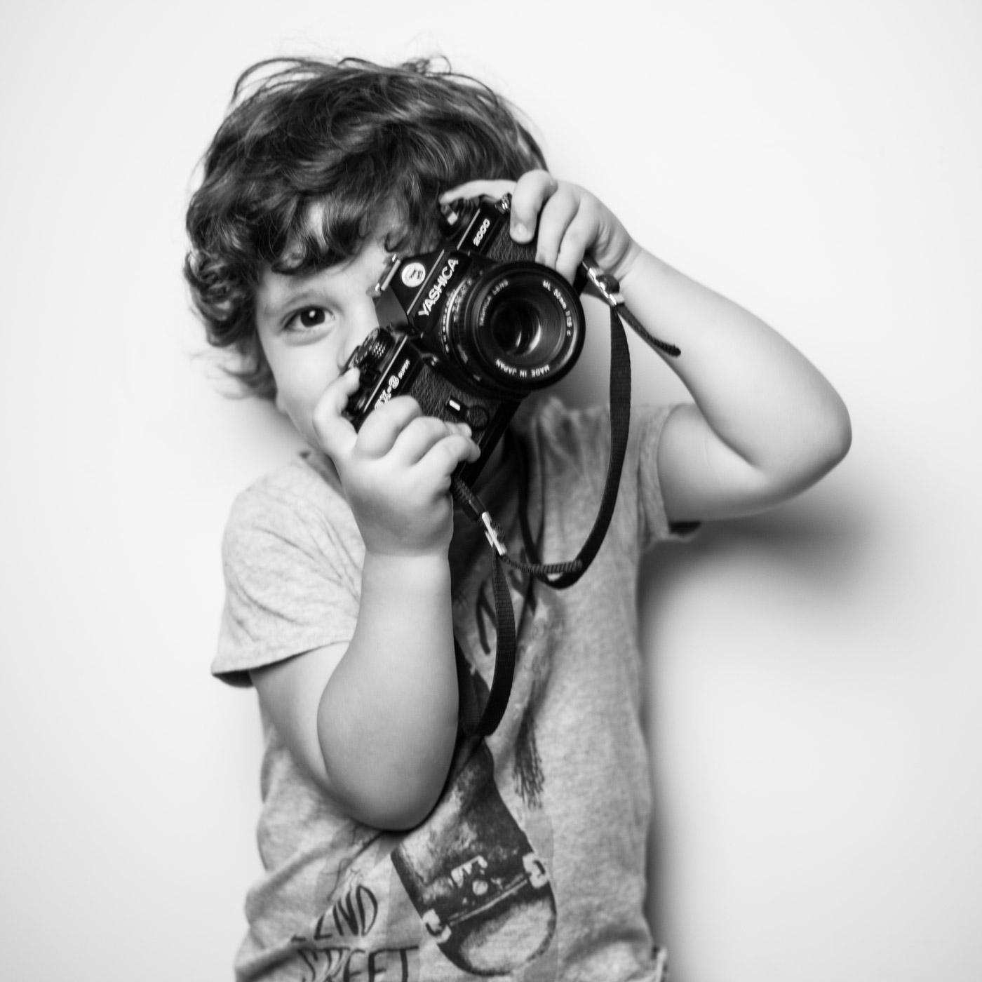 niño sujetando una reflex yashica con actitud de fotografo profesional
