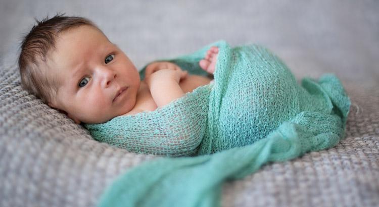 bebé con un wrap azul en una fotografía newborn