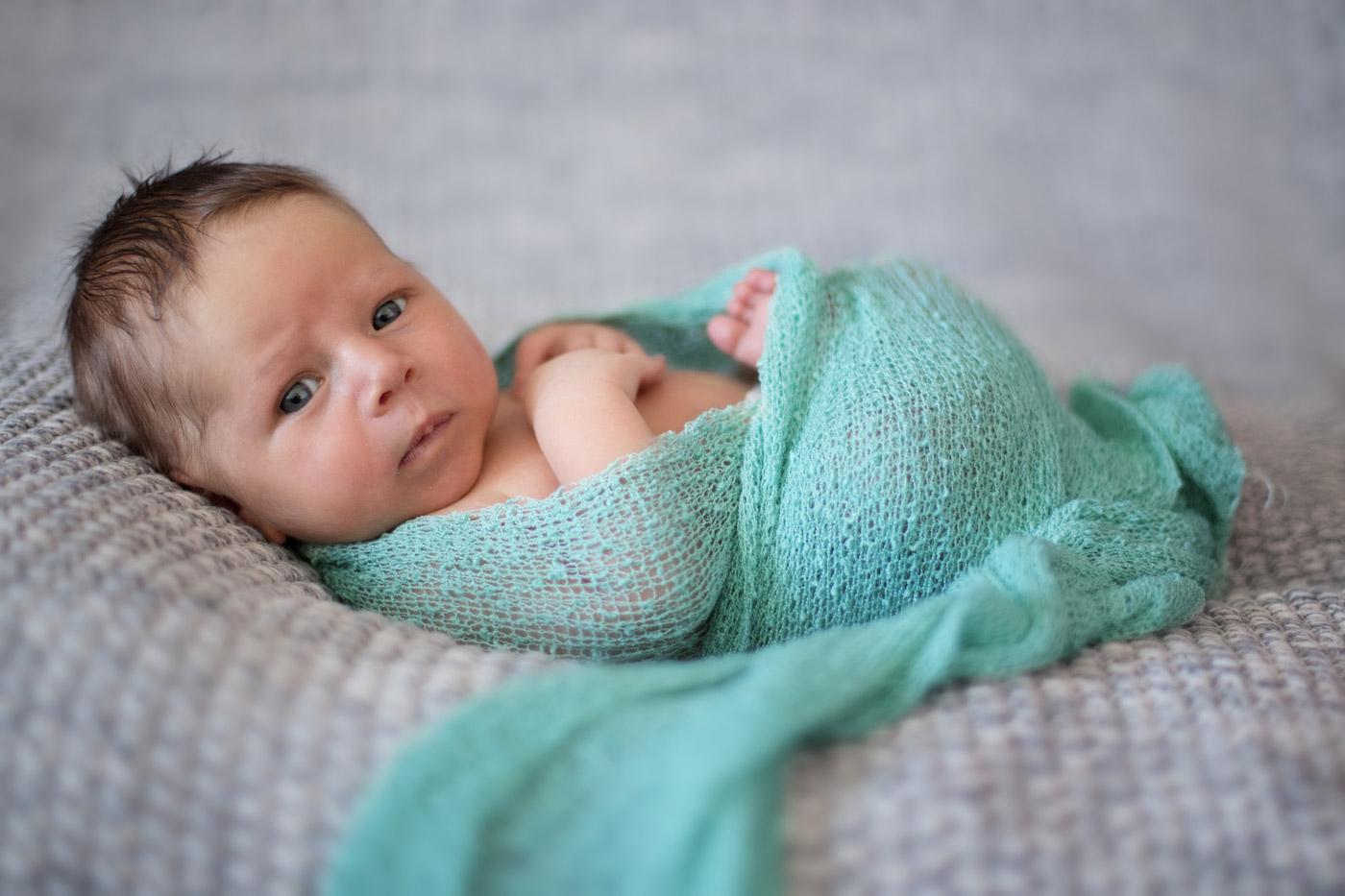 bebé envuelto en un wrap azul newborn