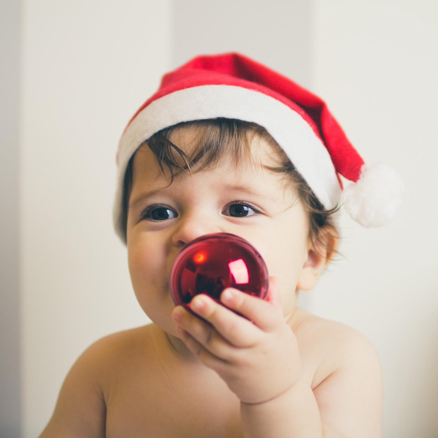 niño con gorro de navidad sujetando un bola roja del arbol de navidad