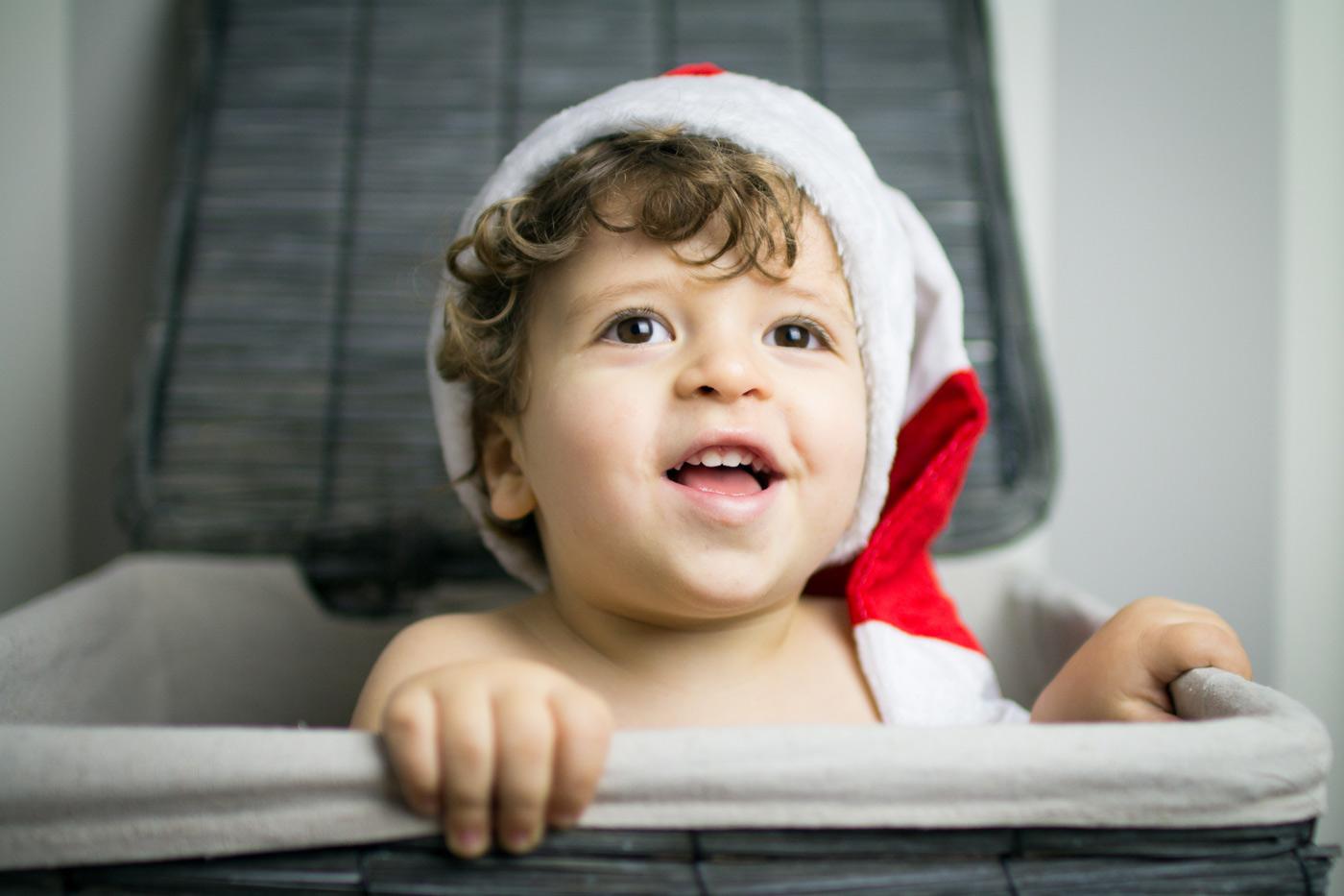niño sonriendo escondido en la cesta de la colada con un gorro de navidad