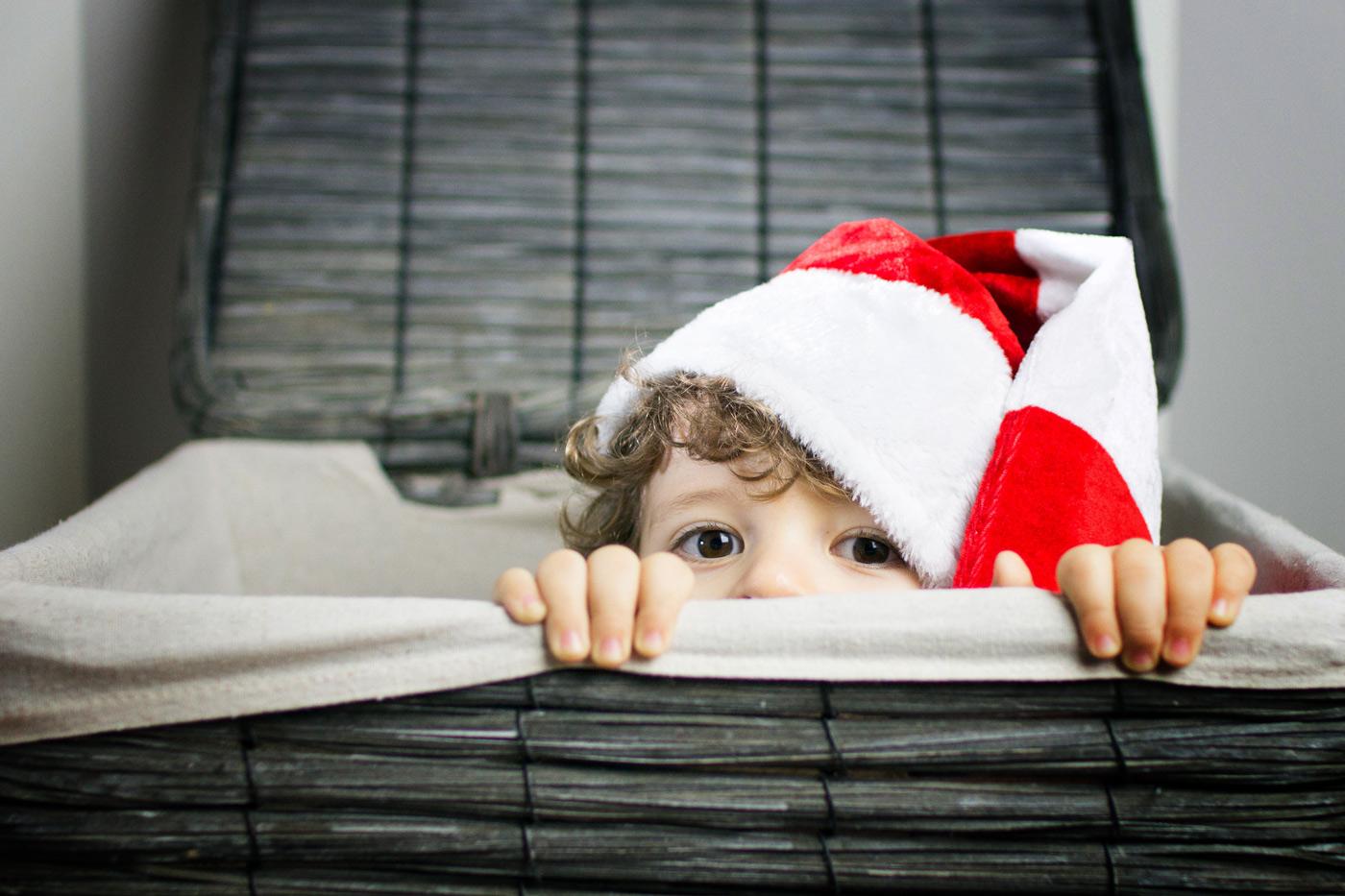 niño en la cesta de la colada con un gorro de navidad