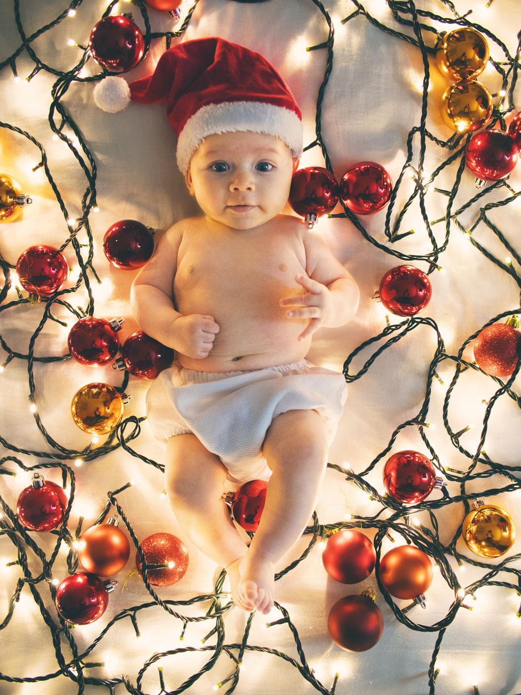 bebe en la cama rodeado de adornos y luces de navidad