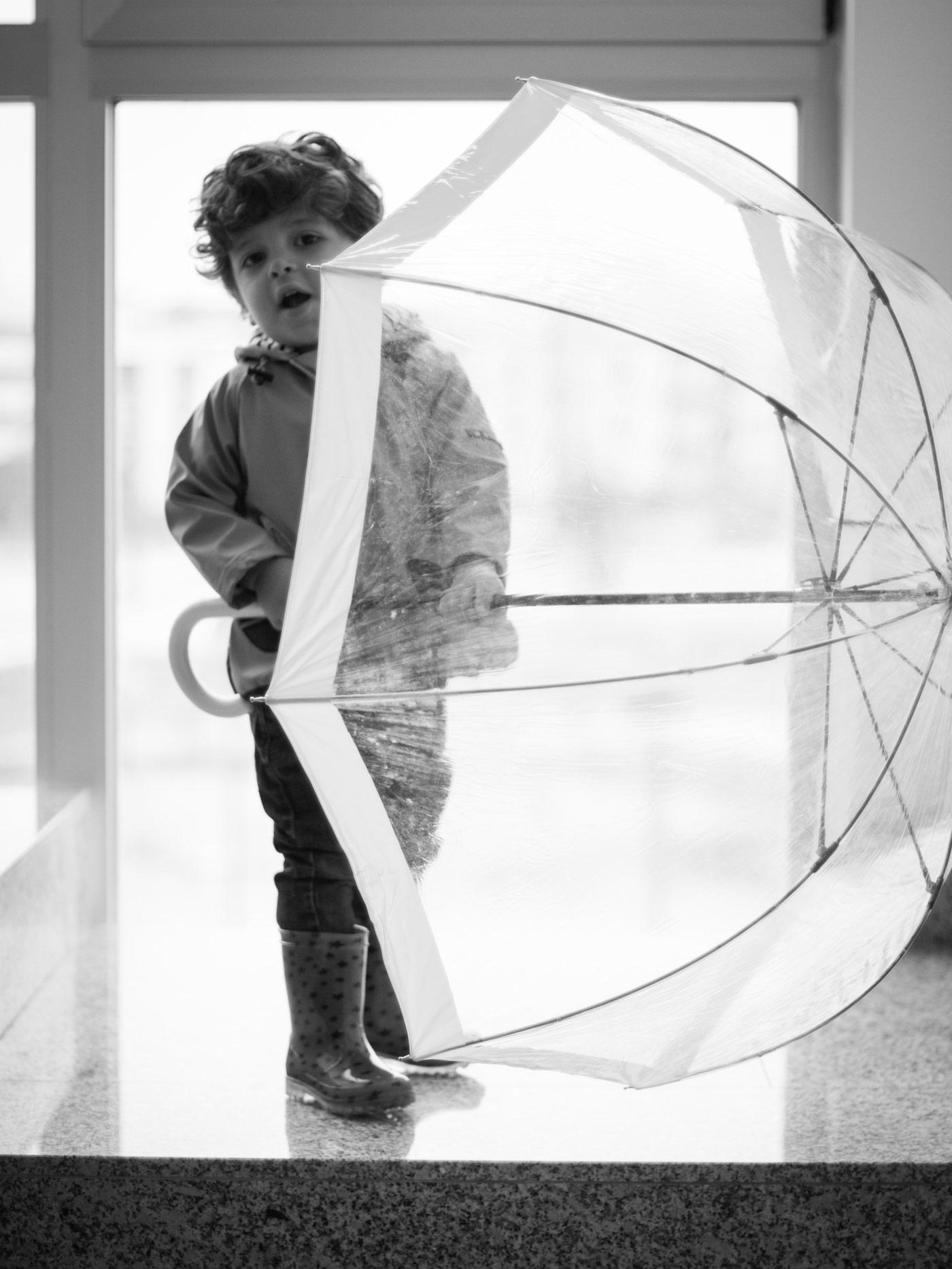 retrato en blanco y negro de un niño en la escalera de un portal con un paraguas abierto