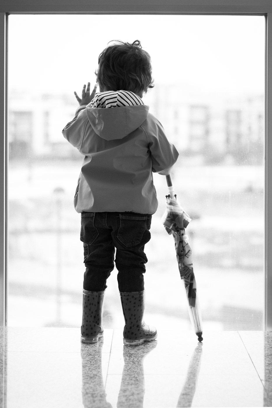 retrato en blanco y negro de un niño de espaldas mirando por un enorme ventanal con un paraguas cerrado en la mano