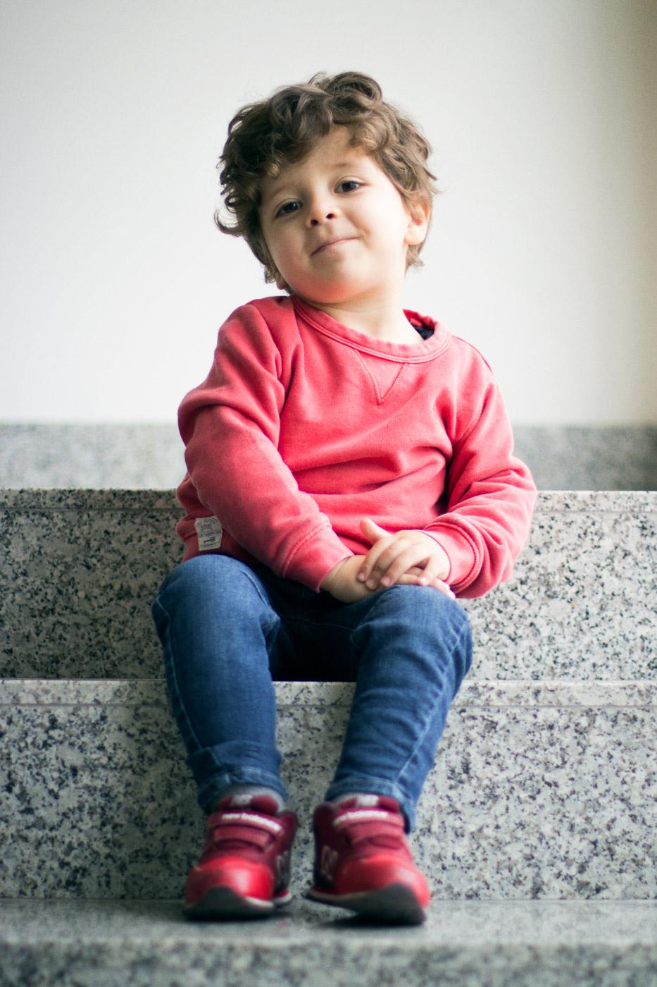niño con jersey rojo sentado en los escalones de una escalera