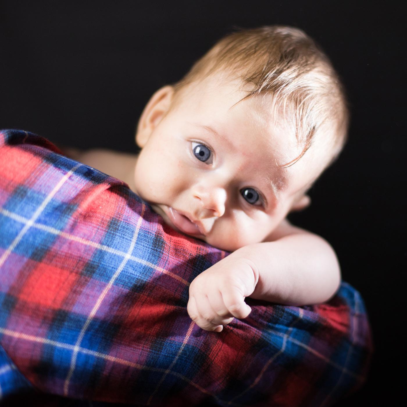 primer plano de un bebe en brazos de su madre con una camisa de cuadros y un fondo negro