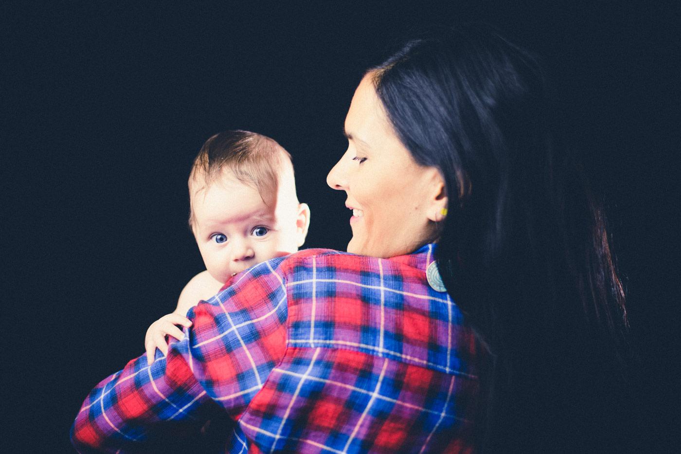 bebe en brazos de su madre con una camisa de cuadros rojos y en un fondo negro