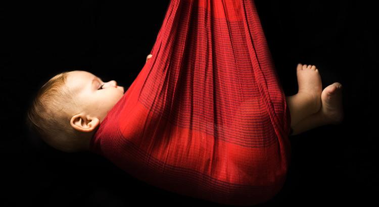 bebe colgando de un foulard rojo en fondo negro