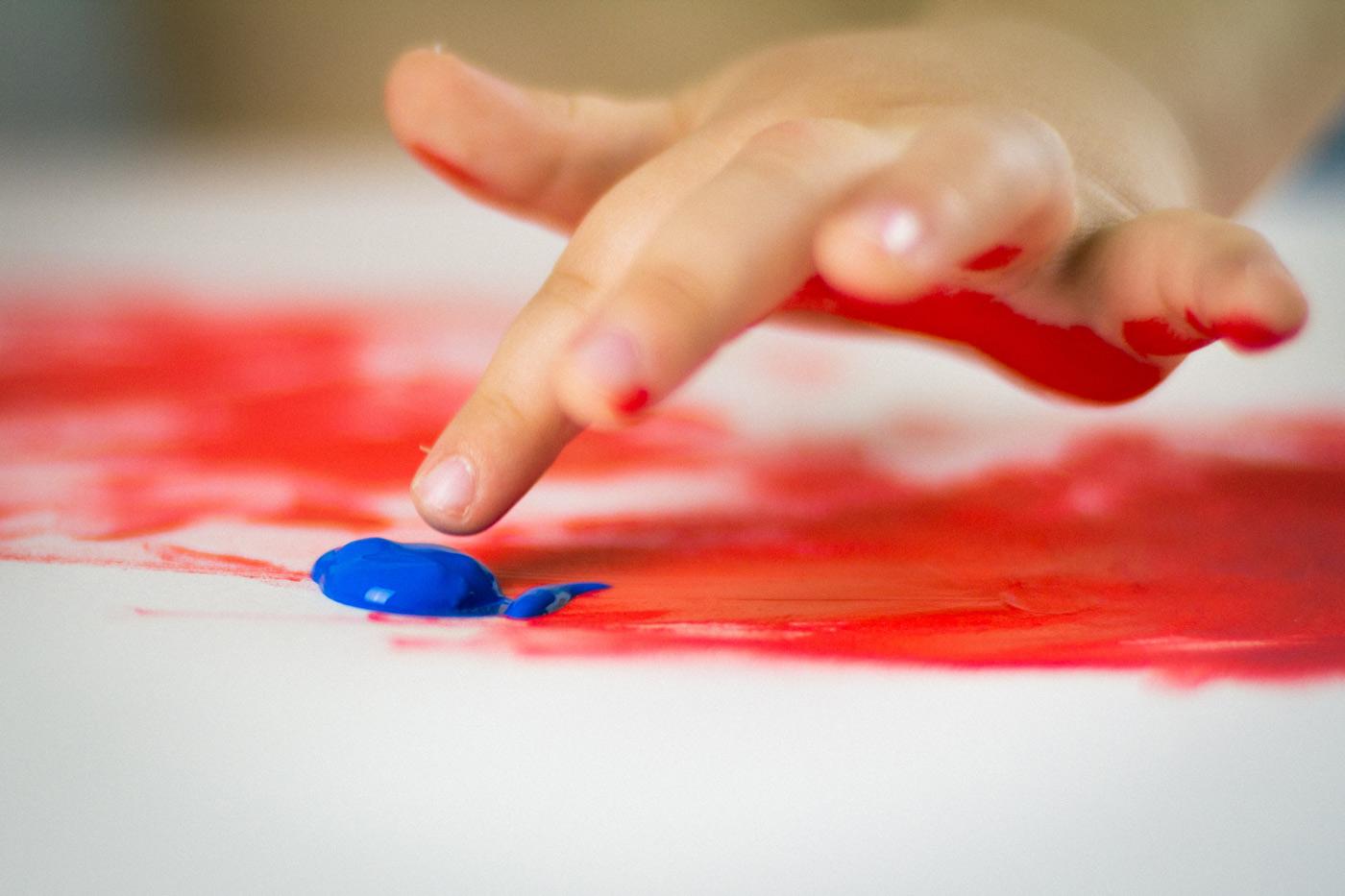 primer plano de una mano de niño pintando con colores rojo y azul