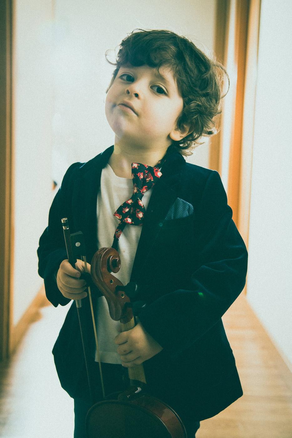 niño interesante que sujeta un violin
