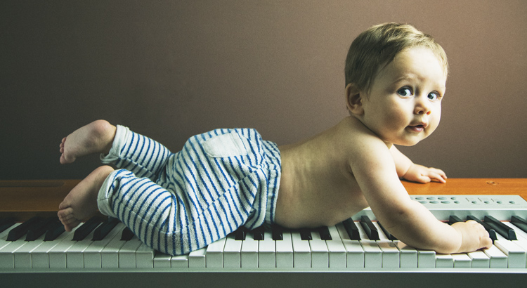 bebe tumbado poca abajo encima de un piano