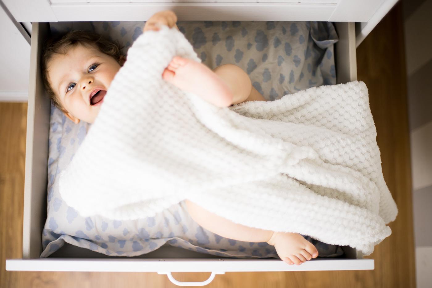 plano cenital de un bebe tumbado dentro un cajon de armario de ikea cubierto por una manta
