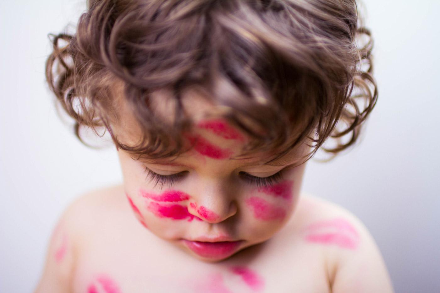 niño de dos años lleno de besos con un pintalabios