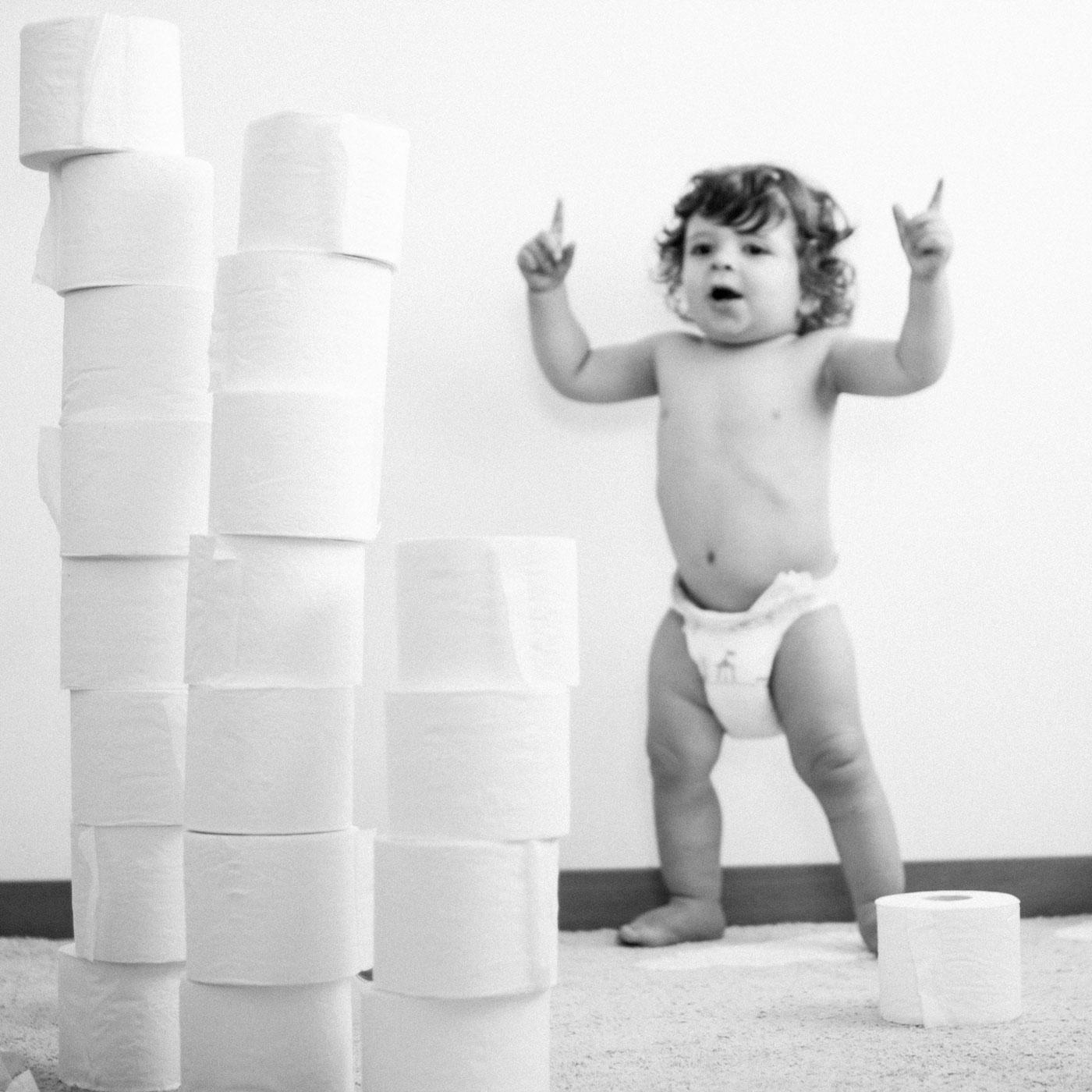 bebe jugando con una torre de papel higienico
