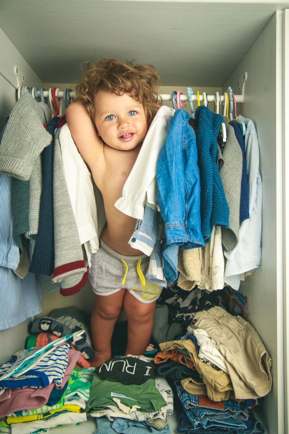 niño de dos años de pie en un armario con ropa