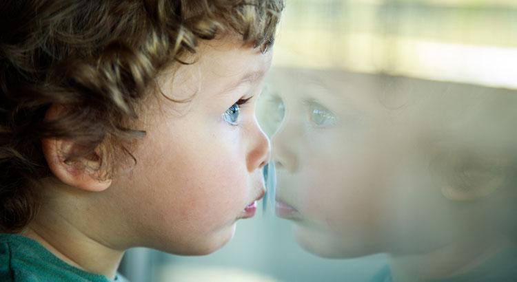 niño de dos años que se refleja en una cristalera